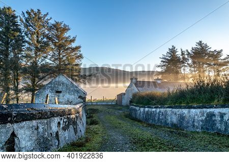Street View Of Typical Irish Cottage In The Fog In County Donegal - Ireland