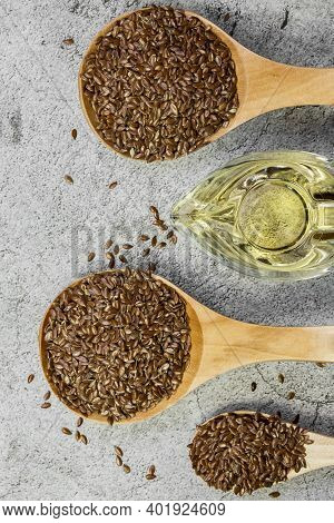 Linseed Oil, Flax Seeds In A Wooden Spoon, Salad Dressing In A Gravy Boat A Source Of Omega-3 Antiox