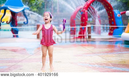 Funny Girl. Cute Asian Kid Playing In The Water Park. Child Laughed. Children Was Wearing A Red Bath