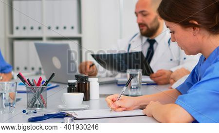Close Up Of Nurse Taking Notes On Clipboard While Radiologist Coworkers Discussing In Background Ana