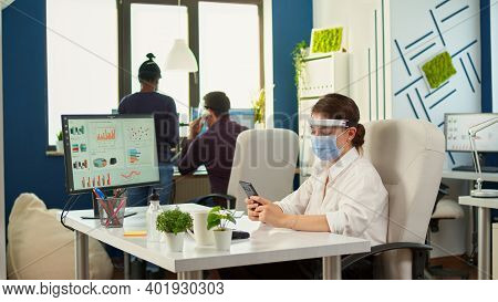 Businesswoman Chatting Using Phone In Office Room Sitting At Desk Wearing Face Mask And Visor While