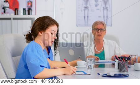Nurse Checking List Of Patients During Brainstorming, Discussing With Colleagues And Taking Notes On
