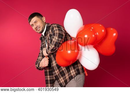 A Guy Wrinkles His Face Carrying A Bunch Of Red Heart-shaped Balloons On Red Background. St.valentin
