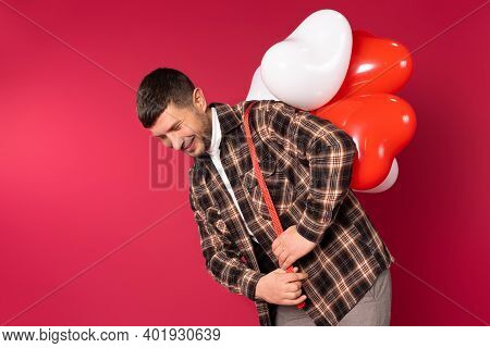Young Cute Man Carries A Bunch Of Heart-shaped Balloons On His Back. St.valentines Day On Red Backgr