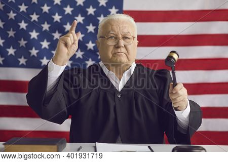 Serious American Judge Holding Gavel And Pronouncing His Sentence In A Court Of Law