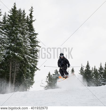 Full Length Of Male Skier Skiing On Fresh Powder Snow With Coniferous Trees And Sky On Background. M
