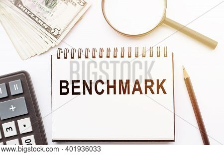 Benchmark - Text Written On A Notebook With Office Background