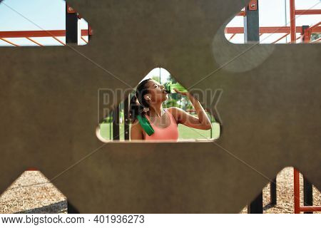 Thirsty Sportive Young Woman Taking A Break And Drinking Water After Training At Outdoor Gym. View T