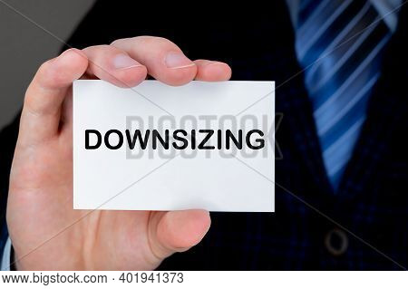Businessman Holding Paper Visiting Card With Downsizing Text On It. Business Concept.