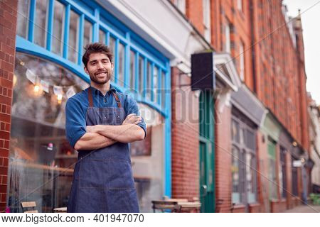 Portrait Of Male Small Business Owner Wearing Apron Standing Outside Shop On Local High Street