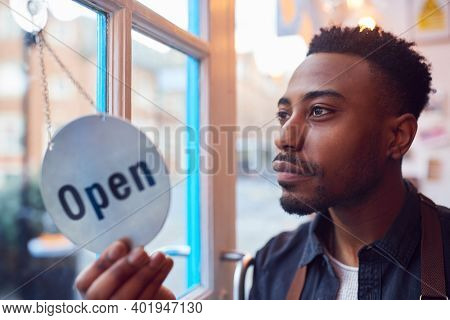 Small Business Owner Turning Around Open Sign On Shop Or Store Door