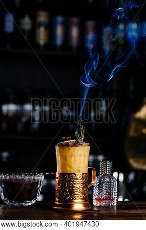 Alcoholic Cocktail With Orange On Wooden. Yellow Cocktail With A Smoking Garnish With Copy Space. Ve