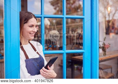 Female Small Business Owner With Digital Tablet Standing In Shop Doorway On Local High Street