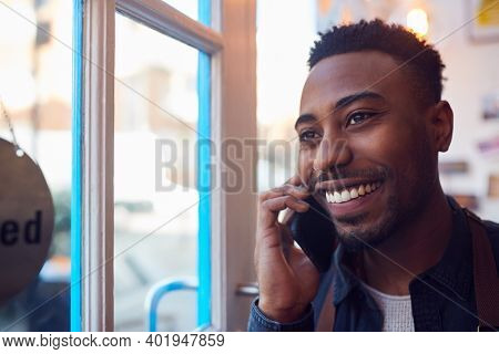 Small Business Owner Standing By Shop Door Making Call On Mobile Phone