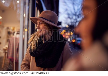 Evening View Of Two Women Window Shopping Looking At Display In Fashion Store