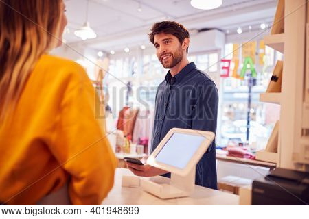 Female Small Business Owner Accepting Contactless Payment In Shop From Customer Using Mobile Phone