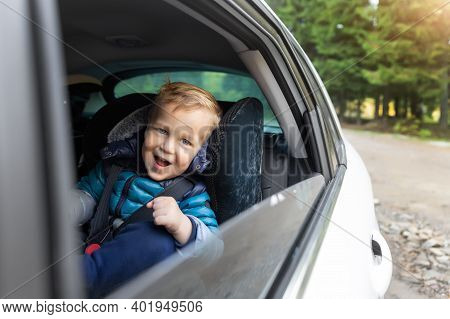 Little Cute Adorable Happy Caucasian Toddler Boy Sitting In Child Safety Seat Car Open Window Enjoy