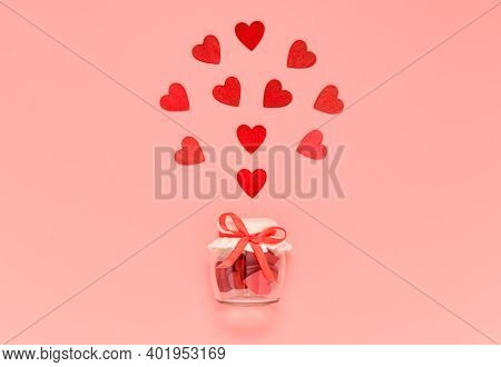 Red Wooden Hearts In Jar With Bow Knot On Pink Pastel Background. Romantic Heart Composition For Val