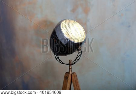 Stylish Lamp On Tripod In Room. Tripod Light Projector. Decorative Light Projector Stands Against A