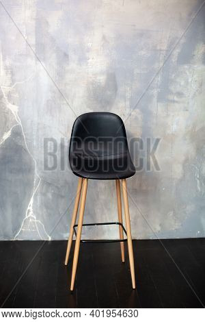 Bar Stool Stands Against A Gray Concrete Wall. Loft Furniture Design. Modern Black Chair Standing In