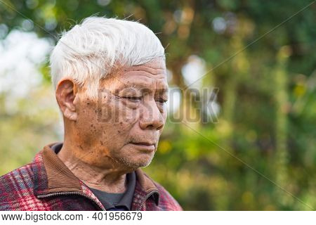 Portrait Of An Elderly Man Worried And Looking Down While Standing In A Garden. Space For Text. Conc