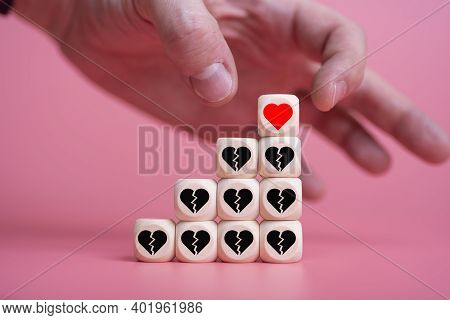 Love Valentine's Day Conceptman Hand Takes The Heart, With A Pyramid Of Other Broken Hearts.