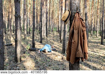 In The Background, Out Of Focus, A Man Is Lying On A Log In The Forest, In The Foreground His Cigare