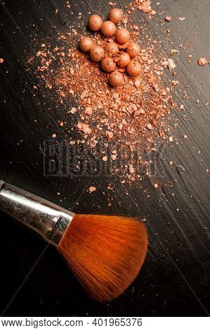 Brushes For Makeup On A Black Background With Beige Powder. Brown Face Powder And Makeup Brushes On
