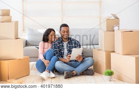 Cheerful Black Couple With Touch Pad To Search For Household Goods For Their New Home Online, Using