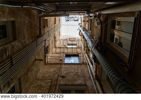 Well In Courtyard Of Old Buildings With Windows, Pipes And Daylight