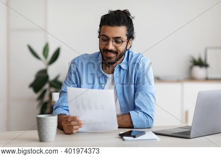 Young Arab Male Self-entrepreneur Working With Papers At Desk In Home Office, Checking Annual Financ