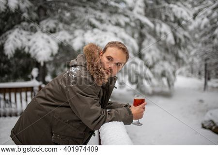 Man Leaning On A Handrail With A Snowy Forest As Background