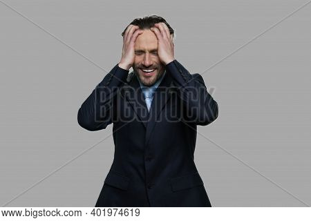 Desperate Businessman Holding Hands On Head. Stressed Frustrated Businessman On Gray Background. Bus
