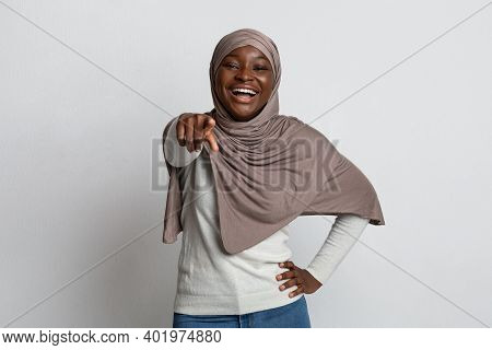 Gotcha. Cheerful Black Muslim Woman In Hijab Pointing Finger At Camera And Laughing, Emotional Afric