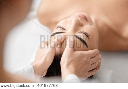 Young Attractive Korean Woman Getting Acupressure Head Massage Treatment In Spa Salon. Professional
