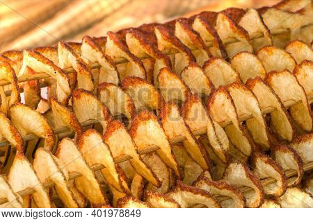 Fried Potatoes On Wooden Sticks. Deep-fried Dishes. Close The Background. Fried Golden Potatoes.