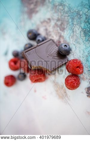 Bitten Chocolate Bar And Berries On A Colorful Placemat