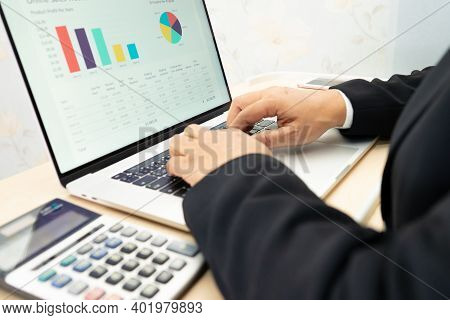 Asian Accountant Working And Analyzing Financial Reports Project Accounting With Chart Graph And Cal