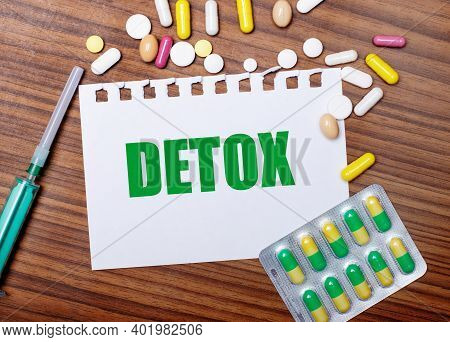 On A Wooden Table, A Syringe, Pills And A Sheet Of Paper With The Inscription Detox. Medical Concept
