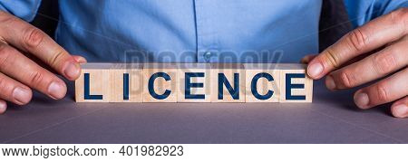 The Word Licence Is Made Up Of Wooden Cubes By A Man. Business Concept
