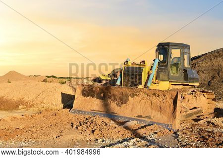 Dozer On Earthmoving At Construction Site On Awesome Sunset Background. Construction Machinery And E