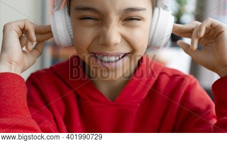The Girl In Headphones Smiles Funny And Wrinkles Her Nose. Modern Technology Concept.