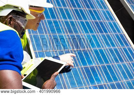 Selective Focus At Digital Tablet. African And Caucasian Engineer Inspect Electrical Solar Panel And