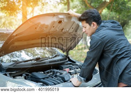Man Open Car Hood For Repair As Maintenance Service. Man Trying To Repair A Car Engine, Looking Insi