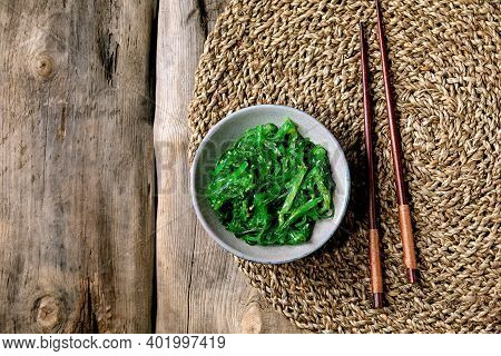 Japanese Wakame Chuka Seaweed Salad With Sesame Seeds In Ceramic Plate With Chopsticks Over Old Wood