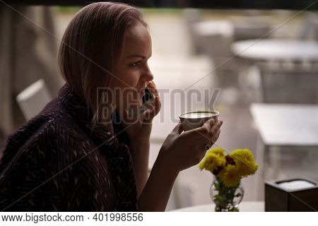 Close-up Portrait Of Smiling Woman Drinking Coffee Alone While Talking On Smartphone. Lovable Lady S