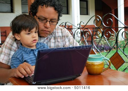 Hispanic Father And Son Using A Laptop Together