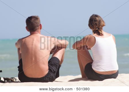 Adult Couple Sitting On The Beach