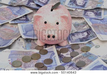 Piggy bank over notes and coins