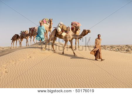 Caravan with bedouins and camels on sand dunes in desert at sunset. Thar desert or Great Indian desert. poster